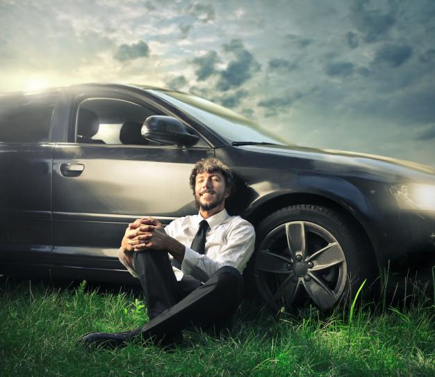 Homem relaxando ao lado do carro com seguro.