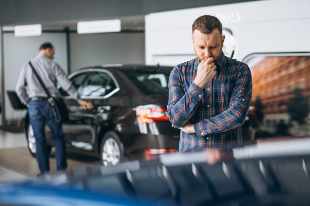 homem pensando em que carro popular comprar
